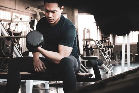 Young man exercising building muscles at the gym