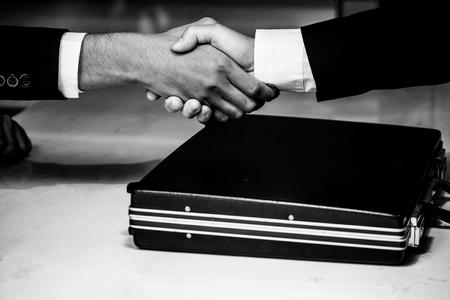 Geschäftsmann, der etwas in einer Aktentasche gibt, während er den Deal zum Abschluss der Vertragsvereinbarung erfolgreich macht