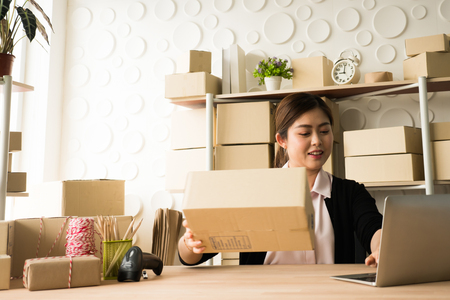 Freelance asian woman working at home with laptop for online marketing packing boxes delivery. Stockfoto