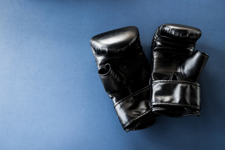 black leather boxing gloves on blue background.