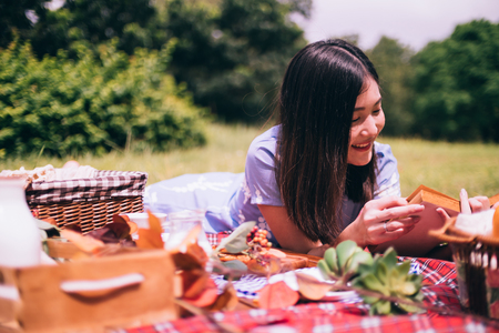 Portrait of beautiful woman enjoying picnic in a park. Stock Photo