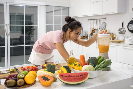 Beautiful young woman making fresh juice from vegetables and fruits in kitchen at home. Stockfoto