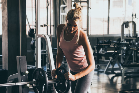 Young woman preparing for training by using barbell at the gym. Stock Photo