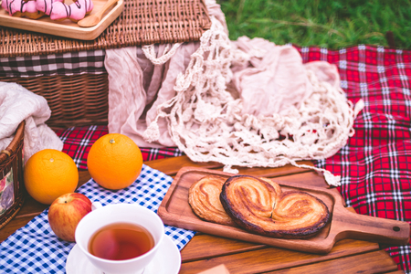 Summer picnic with a basket of food on blanket in the park. Stock Photo