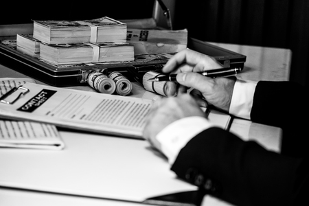 Close up business man signing contract making a deal, case full of money on the desk. black and white tone Stock Photo