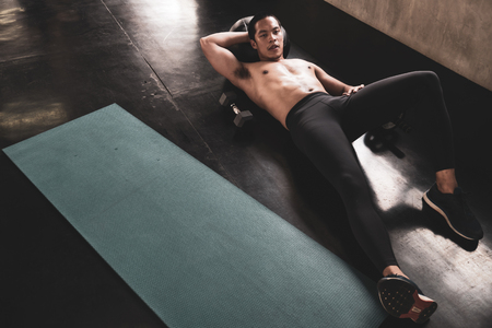 Handsome muscular athletic man taking a break after working out in the gym Stock Photo