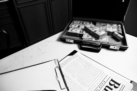 Case full of money, newspaper and document on the desk