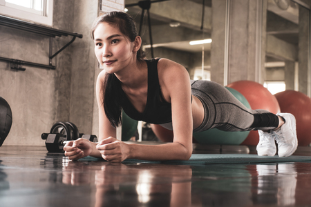 Young woman exercising building muscles at the gym Stock Photo