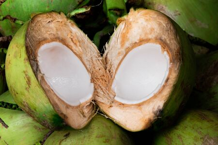 Fresh young coconut split in half showing white flesh with pile of coconuts Stockfoto