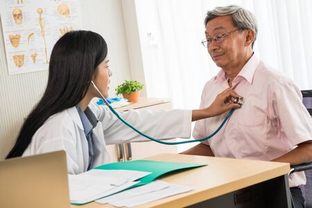 Doctor listening to patients heart rate with stethoscope in medical office