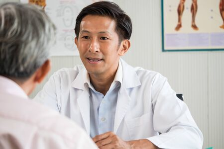 Doctor talking to senior man about his health care in medical office Stockfoto