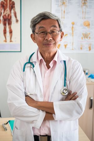 Portrait of senior man doctor standing in medical office
