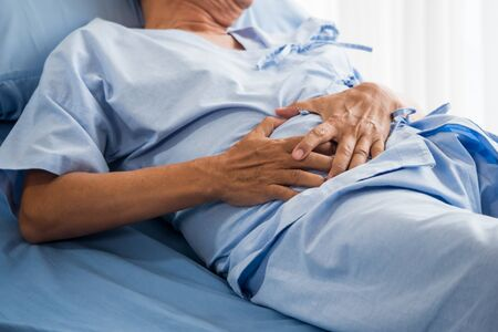 Senior male patient having stomach ache on bed Stockfoto