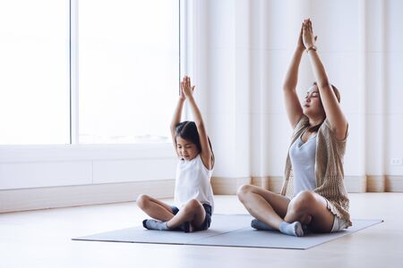 Asian mother and her kid daughter doing stretching exercise at home Stockfoto - 128695056