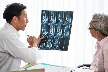 Expert doctor examining and explaining x-ray film to patient Stock fotó