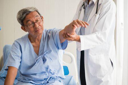 Doctor examining arm of elderly patient in clinic
