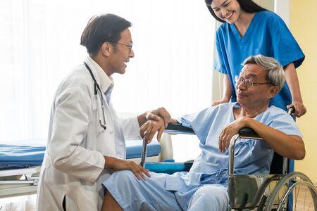 Lekarz i fizjoterapeuta rozmawiają ze starszym pacjentem siedzącym na wózku inwalidzkim