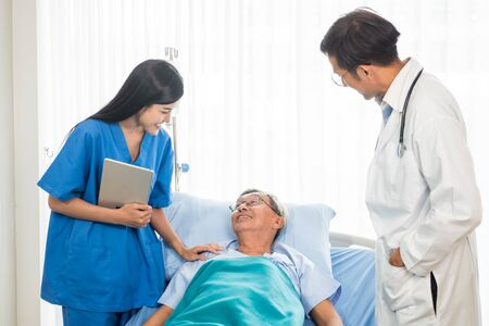Doctor and physiotherapist talking to elderly patient lying on bed Stock fotó