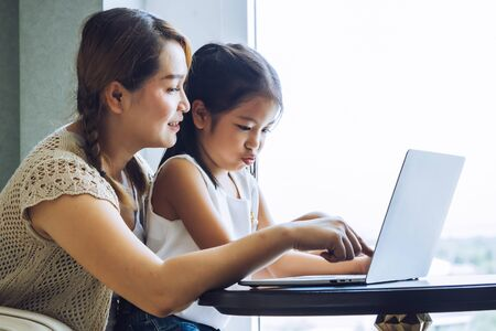 Happy mother with little kid daughter using laptop at home