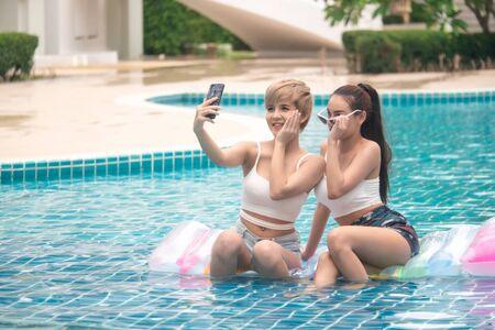 Two cute asian girls having fun in swimming pool at hotel