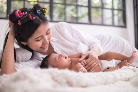 Beautiful young mother with her newborn baby lying in bedroom