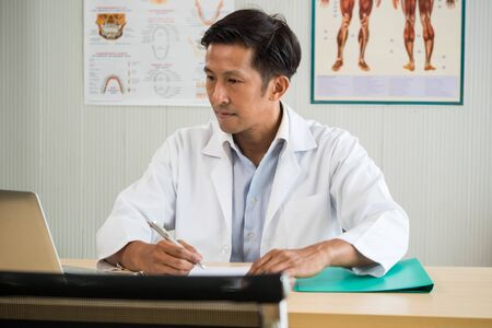Young doctor working on the desk in medical office