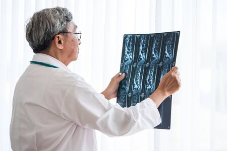 Senior doctor examining x-ray film of patient in examination room