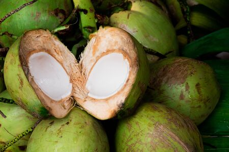 Fresh young coconut split in half showing white flesh with pile of coconuts Stock fotó