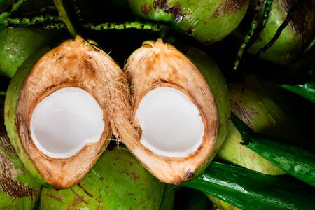 Fresh young coconut split in half showing white flesh with pile of coconuts 版權商用圖片
