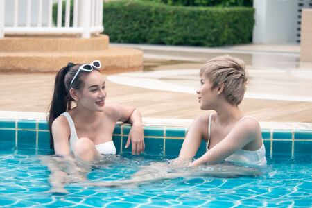 Two cute asian girls having fun in swimming pool at hotel