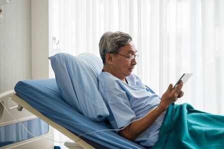 Happy elderly patient sitting on bed and making video call with tablet at hospital