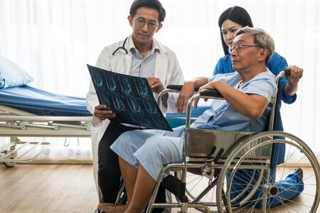 Expert doctor and physiotherapist explaining x-ray film to elderly patient