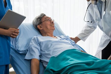 Doctor and physiotherapist talking to elderly patient lying on bed Zdjęcie Seryjne
