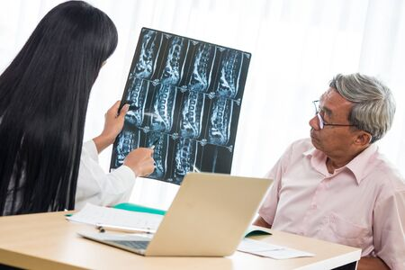 Expert doctor examining and explaining x-ray film to elderly patient in medical office