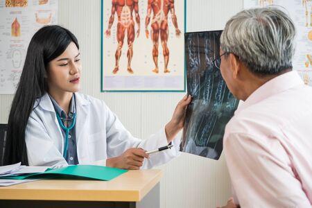 Médico experto examinando y explicando la película de rayos X al paciente anciano en el consultorio médico