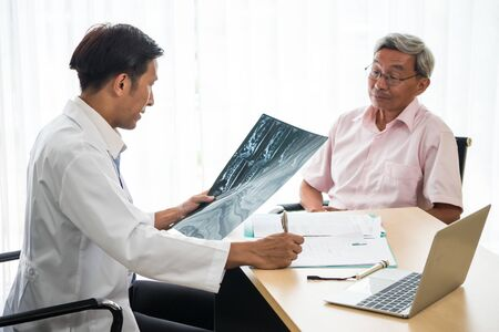 Expert doctor examining and explaining x-ray film to patient