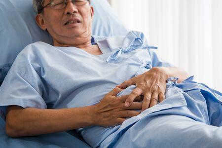 Senior male patient having stomach ache on bed Zdjęcie Seryjne