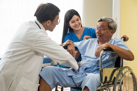 Doctor and physiotherapist talking to elderly patient sitting on wheelchair