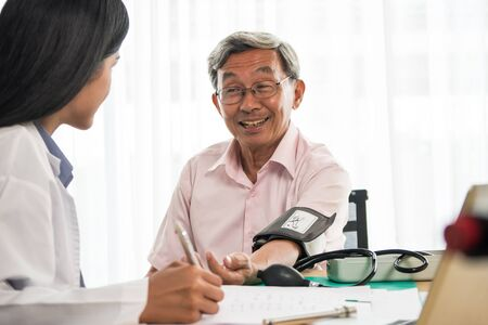 Doctor measuring blood pressure of elderly man in medical office
