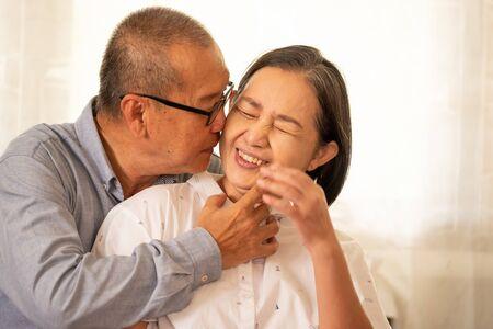 Asian husband kissing on his wife cheek. Banco de Imagens