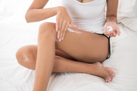 close up of sexy woman applying body lotion  while sitting on the bed.