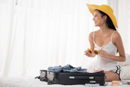 Asian beautiful woman preparing clothes for vacation and sitting on a bed in the bedroom.
