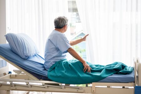 Asian patient man looking outside and sitting on hospital bed in the hospital room.