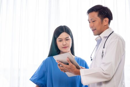 Asian doctor explaining works from tablet to medical assistants. 版權商用圖片