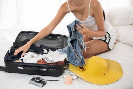 woman preparing clothes for vacation and sitting on a bed in the bedroom.