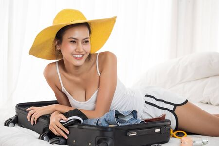 Asian beautiful woman preparing clothes for vacation and lying down on a bed in the bedroom.
