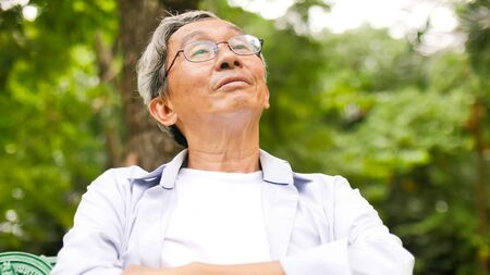 Happy asian man sitting on a bench at the park. Stok Fotoğraf