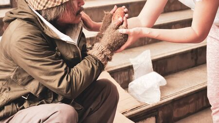 Woman giving food to homeless man who sitting on stairs. Stock Photo