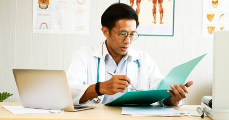 Doctor checking diagnosis results at doctors room. Stock Photo