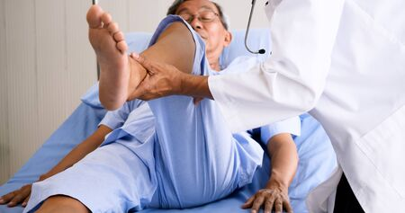 Physical therapist doing physical therapy for adult patient at hospital room. Archivio Fotografico - 135149493